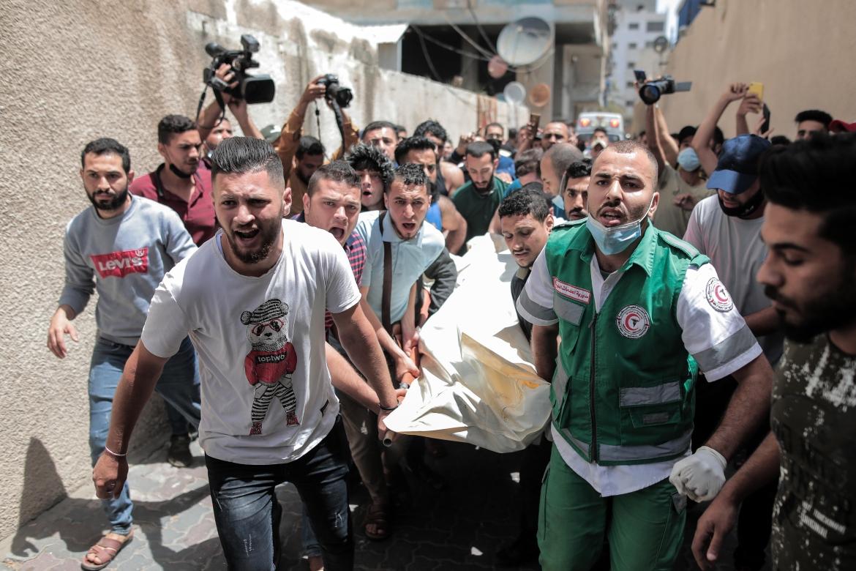 Seorang paramedis dan pria lainnya membawa tubuh seorang anggota Jihad Islam dengan tandu setelah dia terbunuh di apartemennya di gedung alJundi di Kota Gaza  Hosam Salem / Al Jazeera