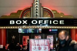 A guest purchases a ticket in front of a box office at AMC movie theatre in Lincoln Square, amid the coronavirus disease (COVID-19) pandemic, in the Manhattan borough of New York City, New York, US, March 6, 2021 [File: Jeenah Moon/Reuters]