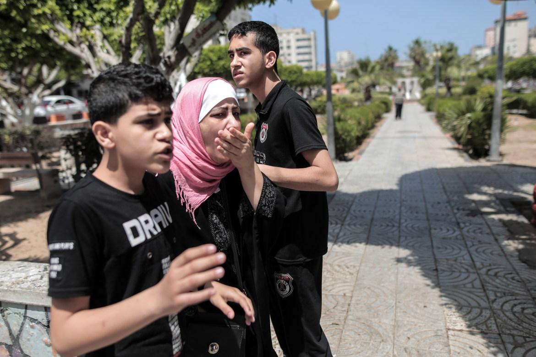Seorang wanita, diapit oleh kedua putranya, menutupi mulutnya dengan syok saat dia memandang di Rimal, Kota Gaza  Hosam Salem / Al Jazeera