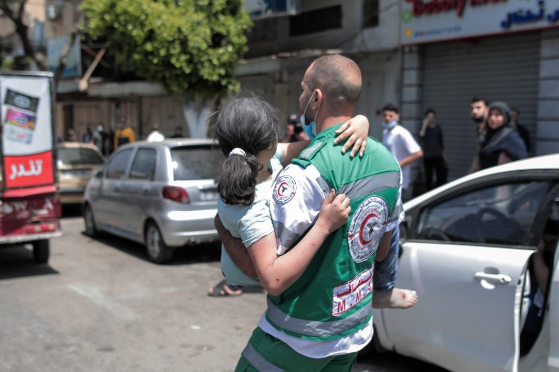 Seorang paramedis membawa seorang gadis tanpa alas kaki yang tinggal di gedung perumahan alJundi di Kota Gaza  Hosam Salem / Al Jazeera