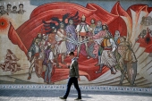 A man passes an ethnic Albanian mural in Skopje, North Macedonia, on October 1, 2018 [File:AP/Thanassis Stavrakis]