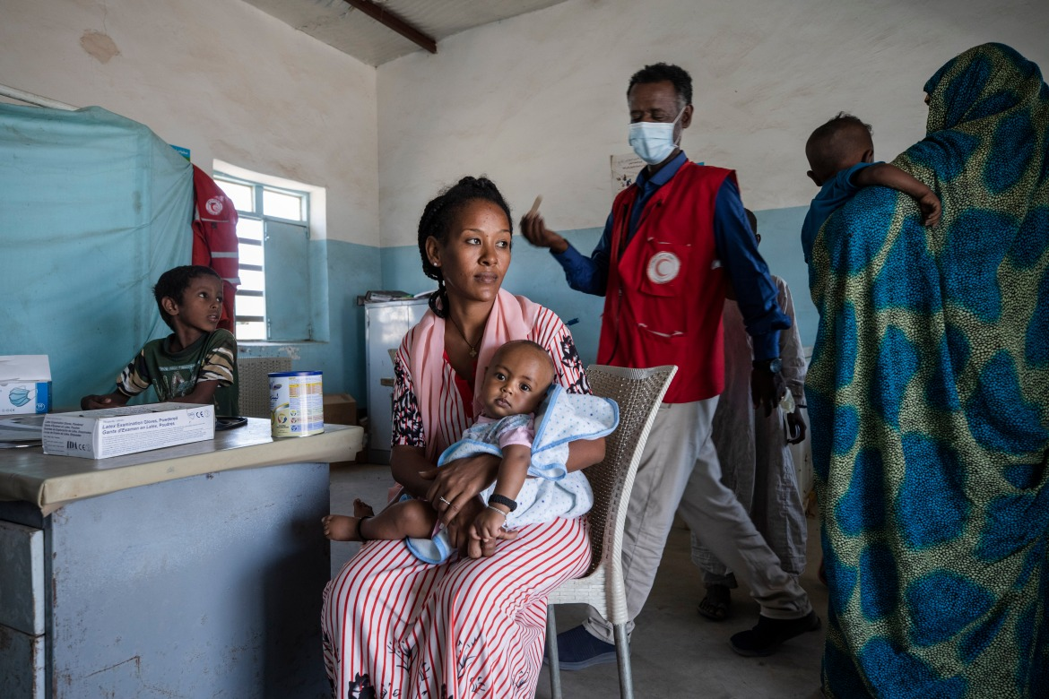 Dr. Tewodros prepares to preform a medical checkup on an infant inside the Sudanese Red Crescent clinic. [Nariman El-Mofty/AP Photo]