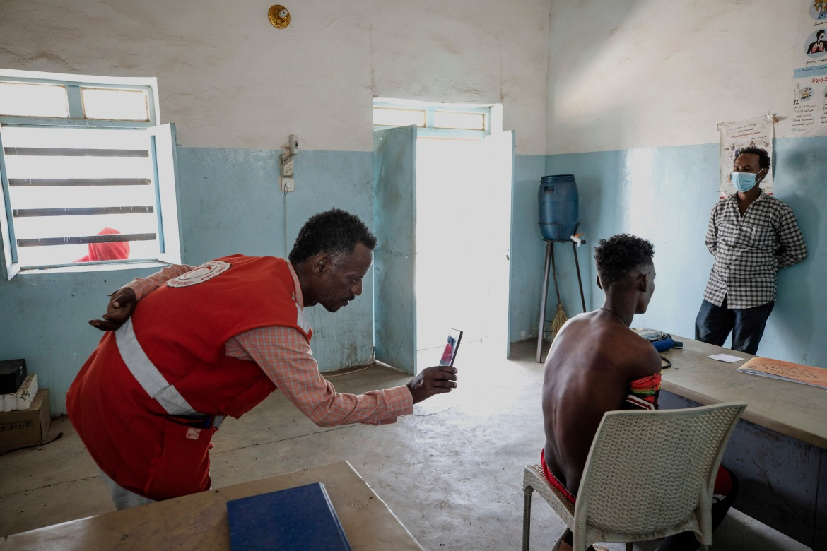 """Dr. Tewodros uses his mobile phone camera to document the welts on the back from a beating by Eritrean soldiers of Adhanom Gebrehanis, a 20-year-old Tigrayan refugee from Korarit village. """"It is definitely genocide,"""" he says. """"If someone is being attacked for their identity, if they're threatened to be vanished because of their identity, there is no other explanation for this."""" [Nariman El-Mofty/AP Photo]"""