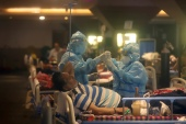 Health workers attend to COVID-19 patients at a makeshift hospital in New Delhi [File: AP]