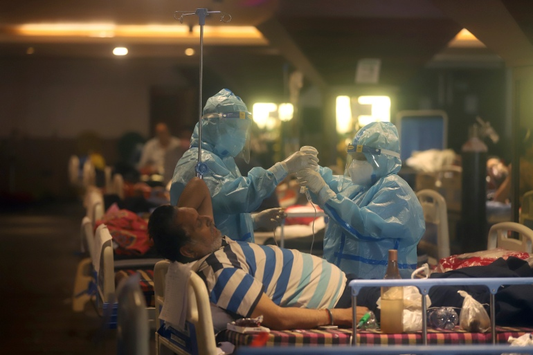 Health workers attend to COVID-19 patients at a makeshift hospital in New Delhi [File: AP Photo]
