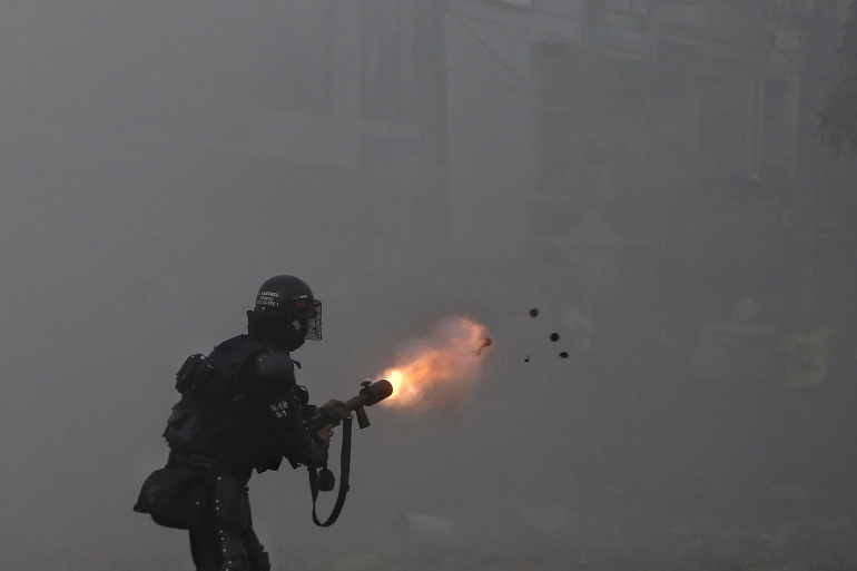 A police officer fires tear gas at protesters during a strike against tax reform in Cali, Colombia [File: Andres Gonzalez/The Associated Press]