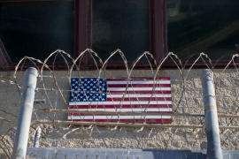 In this photo reviewed by US military officials, an American flag is seen through razor wire on the control tower of the Camp VI detention facility, Wednesday, April 17, 2019, in Guantanamo Bay Naval Base, Cuba [Alex Brandon/AP]