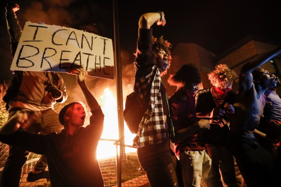 Protesters demonstrate outside a burning Minneapolis Third Police Precinct on May 28, 2020, in Minneapolis [File: John Minchillo/AP Photo]