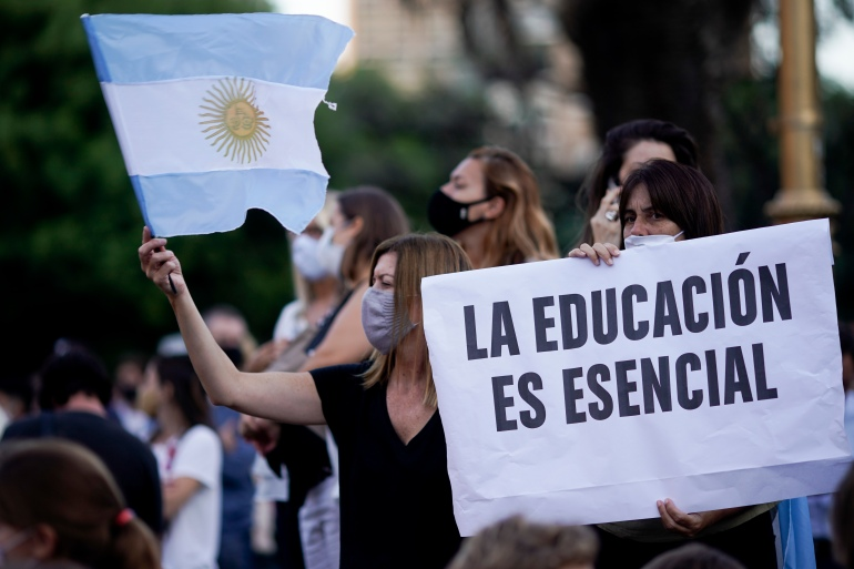 A woman holding a sign reading, 'Education is essential' during a protest outside the Ministry of Education in Buenos Aires after the government suspended in-person classes to curb a spike in coronavirus cases [File: Victor Caivano/AP Photo]