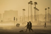 People walk on a beach path as evening winds kick up sand in Long Beach, California. The state lost congressional seats after the latest census data [File: Ashley Landis/AP Photo]