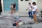 Residents take pictures of blood on the street after a police operation targeting suspected drug traffickers in the Jacarezinho favela of Rio de Janeiro on Thursday [Silvia Izquierdo/AP]