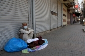 A street vendor waits for customers at a market closed as the government announced new restrictions for the COVID-19 measures, in Peshawar, Pakistan [Muhammad Sajjad/AP]