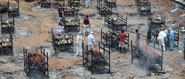 Bodies of people who died of COVID-19 are cremated at an open crematorium on the outskirts of Bengaluru, Karnataka state, India, Wednesday, May 12, 2021. (AP Photo/Aijaz Rahi)