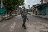 An Indian paramilitary soldier stands guard on a deserted road, as Kashmiris mark Eid during lockdown to curb the spread of coronavirus in Srinagar [File: Dar Yasin/AP]