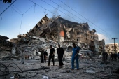 Palestinians walk next to the remains of a destroyed 15-storey building after being hit by Israeli air strikes on Gaza City [Khalil Hamra/AP]