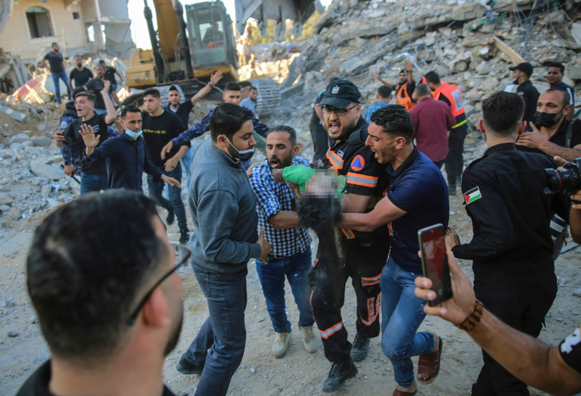 Palestinians carry the body of a child found in the rubble of a house that was destroyed in Israeli air attacks in the town of Beit Lahiya. [Abdel Kareem Hana/AP photo]