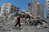 A man walks past the the rubble of the Yazegi residential building that was destroyed by an Israeli airstrike, in Gaza City, Sunday, May 16, 2021. The 57-member Organization of Islamic Cooperation held an emergency virtual meeting Sunday over the situation in Gaza calling for an end to Israel's military attacks on the Gaza Strip [Adel Hana/AP]