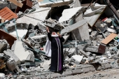 A woman reacts while standing near the rubble of a building that was destroyed by an Israeli airstrike on Saturday that housed The Associated Press, broadcaster Al-Jazeera and other media outlets, in Gaza City [Adel Hana/AP Photo]