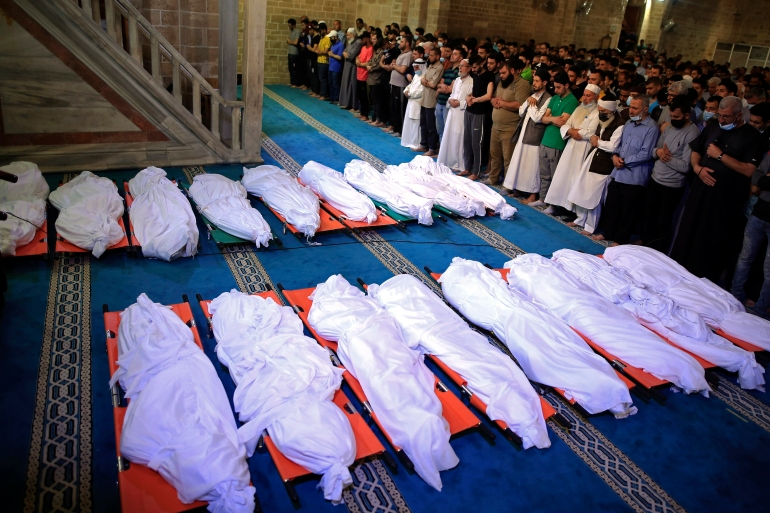 Mourners pray over the bodies of 17 Palestinians who were killed in overnight Israeli air raids in Gaza City on May 16, 2021 [AP/Sanad Latifa]