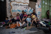 A Palestinian family sits outside their home after it was hit by an early morning Israeli air attack, in Gaza City, Monday, May 17, 2021. (AP Photo/Khalil Hamra)