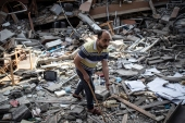 A Palestinian man inspects the damage of a house destroyed by an early morning Israeli airstrike [Khalil Hamra/AP]