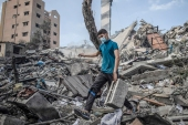 A Palestinian man inspects the damage of a six-story building which was destroyed by an early morning Israeli airstrike, in Gaza City [Khalil Hamra/AP]