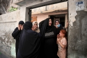 Relatives of Hoda Al-Khozondar, who was killed in an Israeli airstrike, react as mourners carry her body out of the family home, during her funeral in town of Khan Younis, southern Gaza Strip, Thursday, May 20, 2021 [Yousef Masoud/AP]