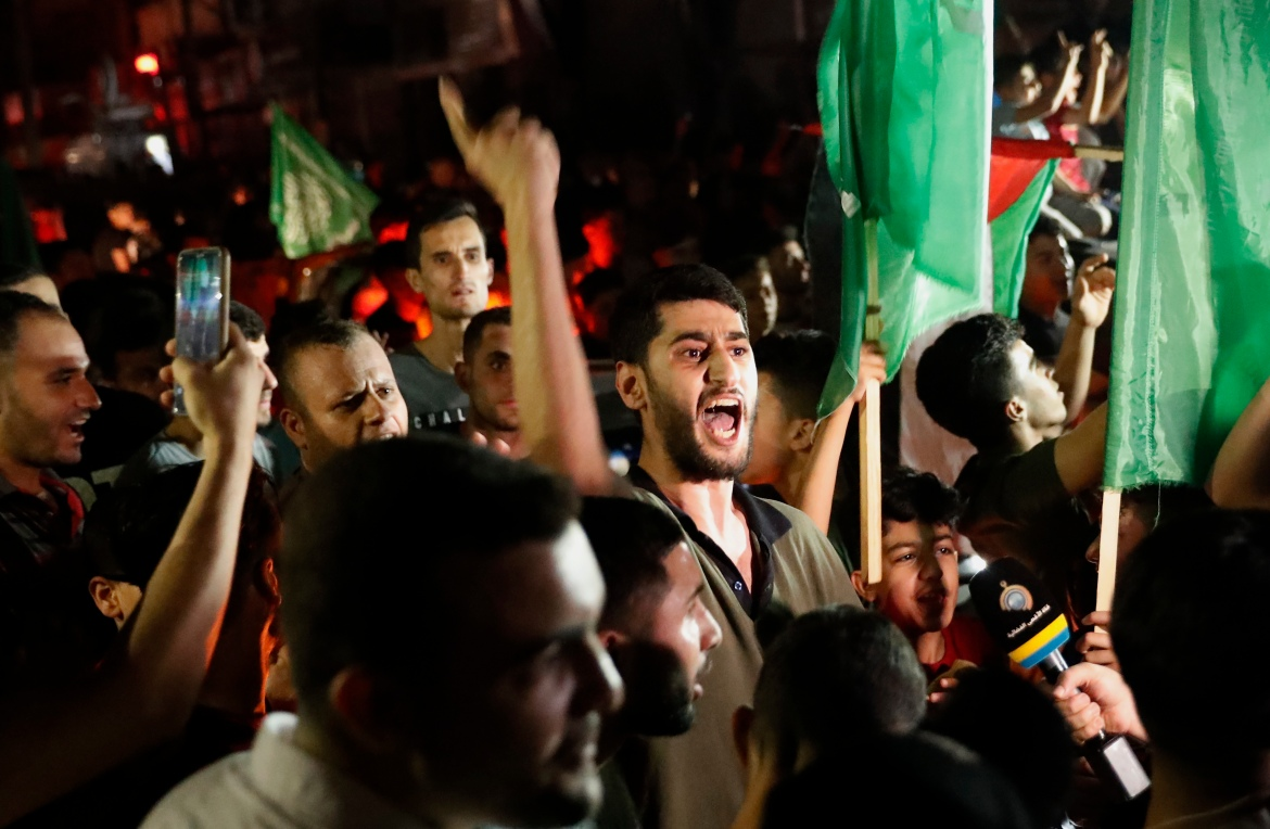 Palestinians in Gaza chant slogans as they wave green Hamas and their national flags. [Adel Hana/AP Photo]