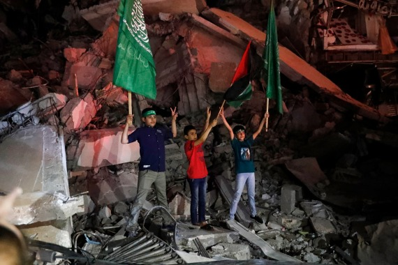 Young men waved Palestinian and Hamas flags, passed out sweets, honked horns and set off fireworks. [Adel Hana/AP Photo]