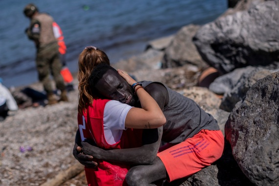 A migrant is comforted by a member of the Spanish Red Cross near the border of Morocco and Spain. [Bernat Armangue/AP Photo]