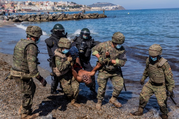 Spanish soldiers expel a migrant from the Spanish enclave of Ceuta. [Bernat Armangue/AP Photo]