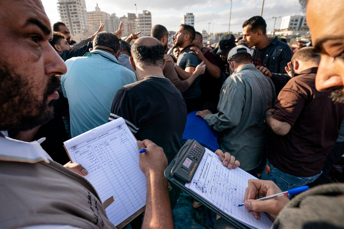 Recorders take down winning bids on fish lots as the day's catch is sold at auction. [John Minchillo/AP Photo]