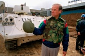 Senator Joe Biden stands in front of a Danish armored personnel carrier at the UN-controlled Sarajevo Airport on April 9, 1993, making a statement about his trip to the besieged Bosnian capital. [File: AP/Michael Stravato]