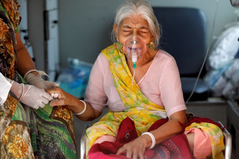 Lilaben Gautambhai Modi, 80, wearing an oxygen mask, sits inside an ambulance as she waits to enter a COVID-19 hospital for treatment in Ahmedabad, India [Amit Dave/Reuters]