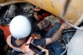 Rescue workers attend to a victim in the rubble at the site of Israeli air strikes in Gaza City on Sunday [Mohammed Salem/Reuters]