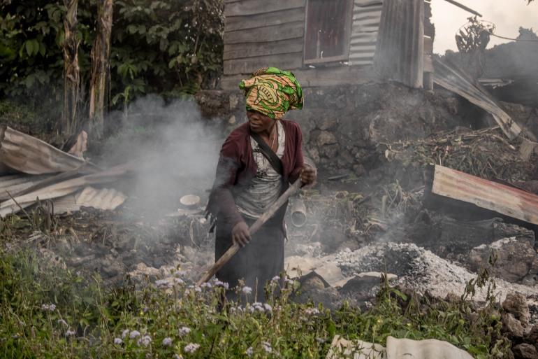 Florence Rudasigara, a victim of the eruption, looks for some metallic goods amongst the ash in her yard [Esdras Tsongo/Al Jazeera]