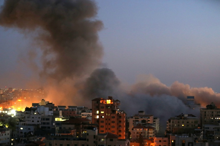Smoke rises from a building in Gaza after it was destroyed by Israeli air attacks on May 11 [Ibraheem Abu Mustafa/Reuters]