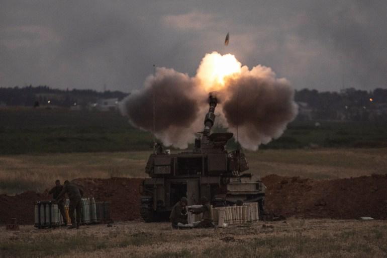 An Israeli artillery unit fires towards the Gaza Strip as the week-long attacks against Palestinians continue [Heidi Levine/AP]