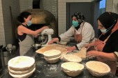 Mavia's bakers prepare dough for the next batch of bread [Maghie Ghali/Al Jazeera]