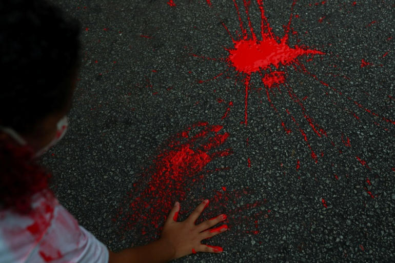 A person places a handprint with red paint on a pavement during a protest in Sao Paulo, Brazil against police violence two days after a police operation in Rio de Janeiro's Jacarezinho favela resulted in the death of 28 people. Sao Paulo, Brazil, May 8, 2021 [Amanda Perobelli/Reuters]
