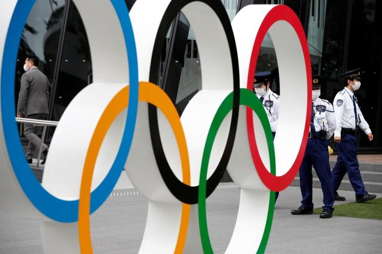 Personel keamanan berjaga di dekat monumen cincin Olimpiade selama unjuk rasa oleh pengunjuk rasa antiOlimpiade di luar markas besar Komite Olimpiade Jepang, di tengah wabah penyakit virus korona COVID19, di Tokyo, Jepang, 18 Mei 2021 Issei Kato / Reuters