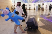 Saudi passengers enter King Abdulaziz International Airport in Jeddah on Monday [Amr Nabil/AP]