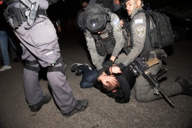 A Palestinian youth is pinned down by Israeli police at a protest against the forcible eviction of Palestinian families [Maya Alleruzzo/AP]