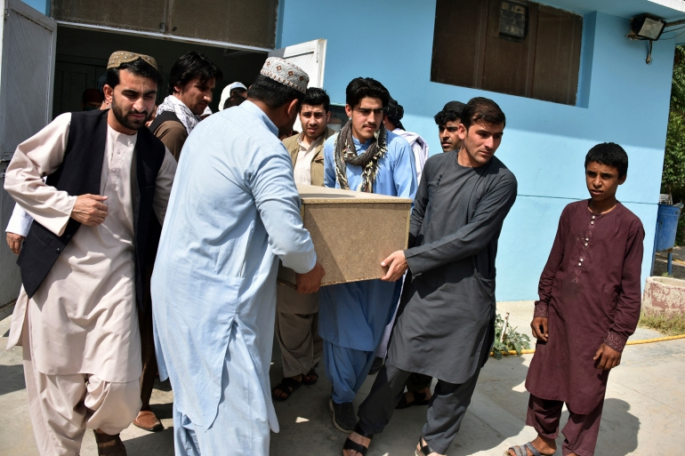 Relatives carry a coffin with the body of television journalist Nemat Rawan he was shot dead by gunmen, in Kandahar province [Javed Tanveer/AFP]