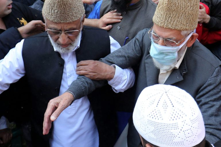 The late Syed Ali Shah Geelani, wearing a mask, with Ashraf Sehrai, who died in jail earlier this year, after their Friday prayers in Srinagar in this 2018 photo [File: Farooq Khan/EPA]