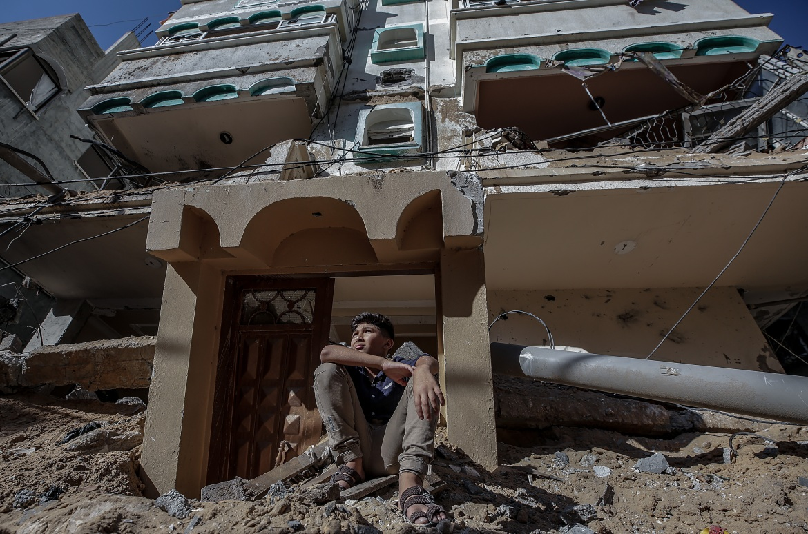 A Palestinian boy sits on the rubble of his home destroyed after an Israeli air attack in Gaza City. [Mohammed Saber/EPA]