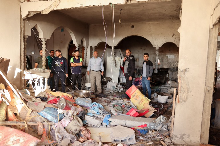 Neighbours and relatives assess the damage inside the house in Deir el-Balah [Said Khatib/AFP]