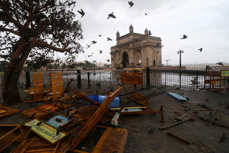 Pigeons fly next to scattered barricades near the Gateway of India monument after strong winds caused by Cyclone Tauktae, in Mumbai [Niharika Kulkarni/Reuters
