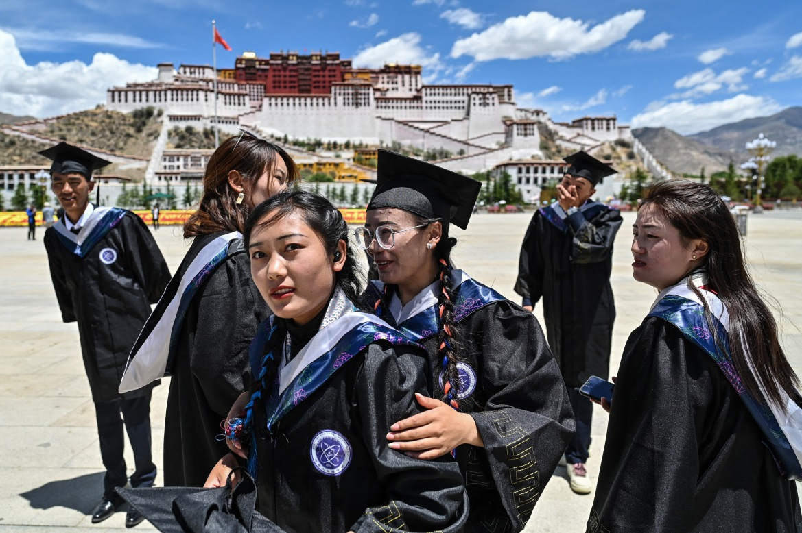 """College of Science graduates from Tibet University celebrate their graduation at the Potala Palace Square. Critics say freedom of movement and expression is tightly controlled amid an ongoing """"Sinicisation"""" of the region. [Hector Retamal/AFP]"""