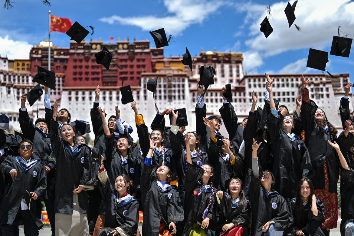 College of Science graduates from Tibet University celebrate their graduation at the Potala Palace Square. [Hector Retamal/AFP]